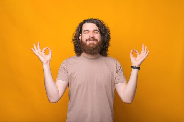 노란색 이상 선 제스처를 만드는 젊은 수염 된 hipster 남자의 초상화