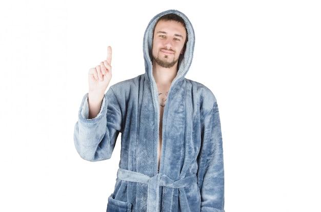 青いバスローブのひげを生やした若者の肖像は分離された注意ジェスチャーを示しています