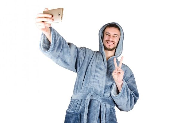 青いバスローブのひげを生やした青年の肖像画は勝利のジェスチャーを示し、selfieになります