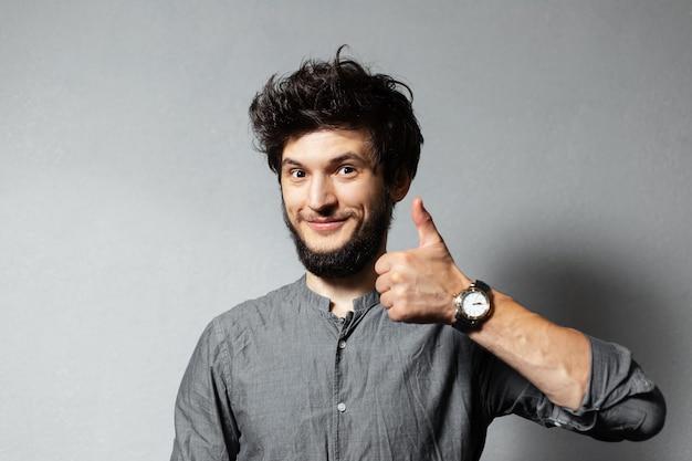 乱れた髪の若いひげを生やした満足している男の肖像画は、灰色の親指を示しています。