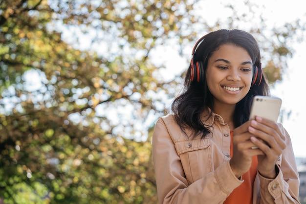 ヘッドフォンで音楽を聴いている若い美しいアフリカ系アメリカ人女性の肖像画