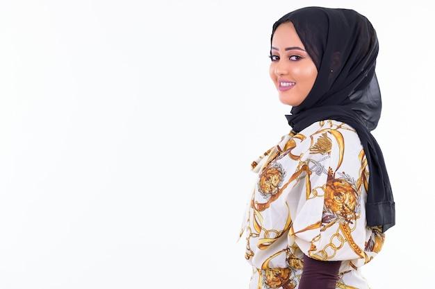 白い壁に隔離されたヒジャーブを身に着けている若い美しいアフリカのイスラム教徒の女性の肖像画