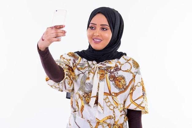 흰 벽에 고립 된 hijab를 입고 젊은 아름 다운 아프리카 무슬림 여성의 초상화