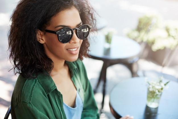 テラスのカフェでリラックスした休憩を笑顔sungassesの若い美しいアフリカ女性の肖像画。