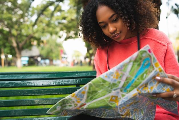 公園のベンチに座って地図を見ている若い美しいアフリカ系アメリカ人女性の肖像画。旅行のコンセプト。屋外。