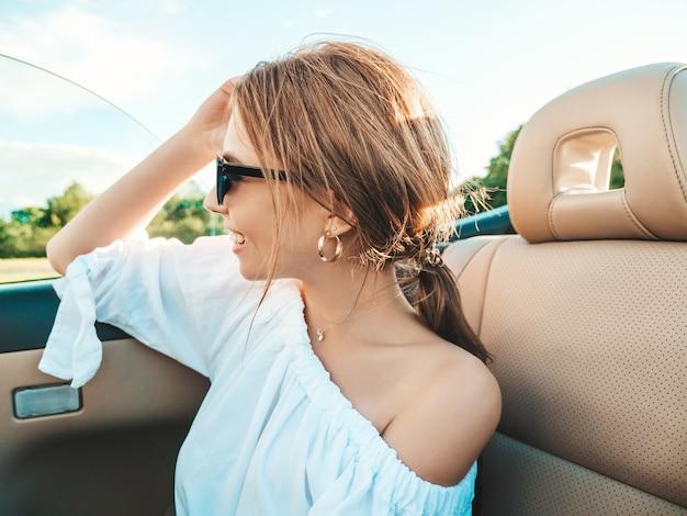 Портрет молодой красивой и улыбающейся хипстерской женщины в кабриолете