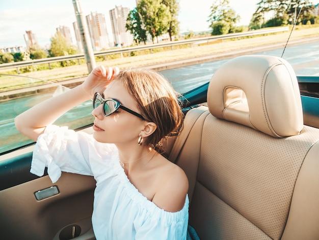 Портрет молодой красивой и улыбающейся хипстерской девушки в кабриолете