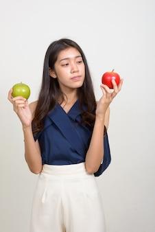 두 사과 사이 선택 젊은 아름 다운 아시아 사업가의 초상화