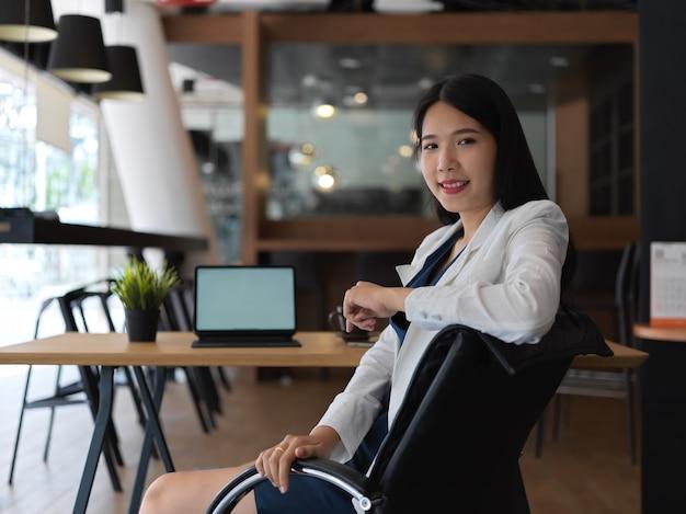 Портрет молодой красивой азиатской коммерсантки, уверенно смотрящей в камеру в ее офисной комнате