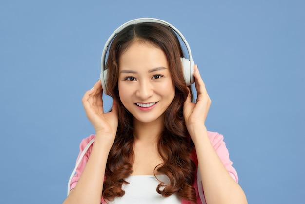 화려한 파란색 배경에서 음악을 듣고 있는 젊은 아름다운 아시아 소녀의 초상화.