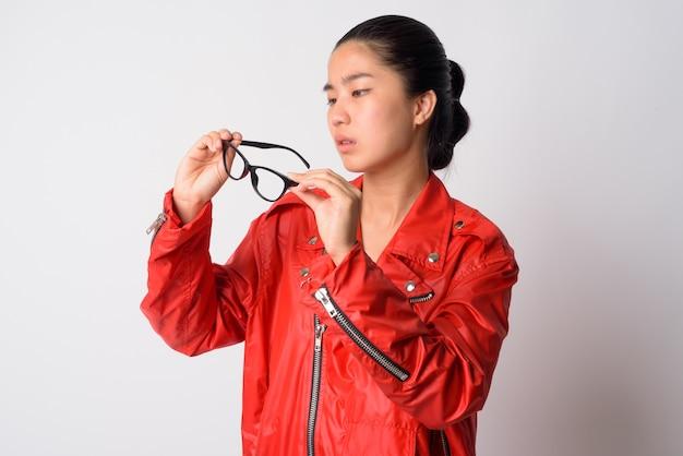 Портрет молодой красивой азиатской мятежной женщины против белой стены