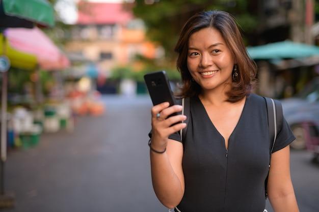 방콕의 거리를 탐험하는 젊은 아름다운 아시아 관광 여자의 초상화