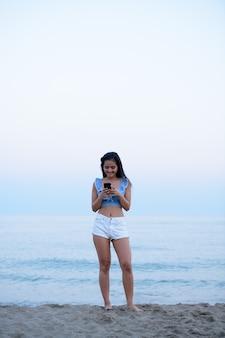 해변에서 편안한 젊은 아름 다운 아시아 관광 여자의 초상화