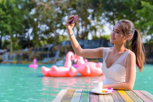 야외 호수에서 편안한 젊은 아름 다운 아시아 관광 여자의 초상화