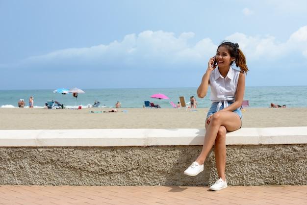 屋外のビーチのそばに座っている若い美しいアジアの観光客の女性の肖像画