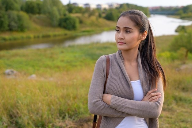 川と緑豊かな緑の野原のリラックスした景色に対する若い美しいアジアの女性の肖像画