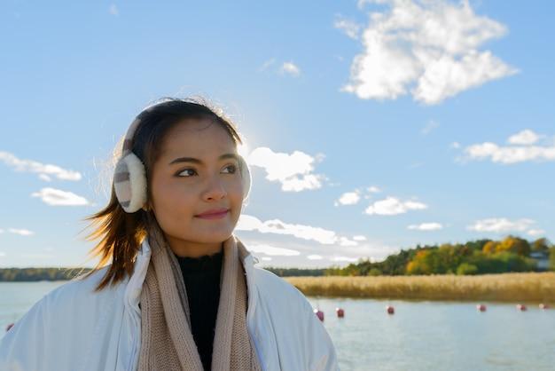 海と澄んだ青い空の美しい景色を背景に若い美しいアジアの女性の肖像画