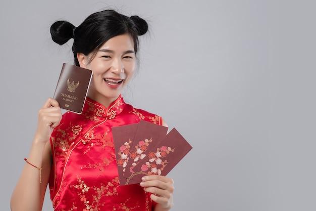 Портрет молодого красивого азиатского платья cheongsam женщины усмехаясь держа красный конверт