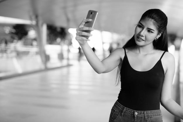 黒と白で街を探索する若い美しいアジアの女性の肖像画