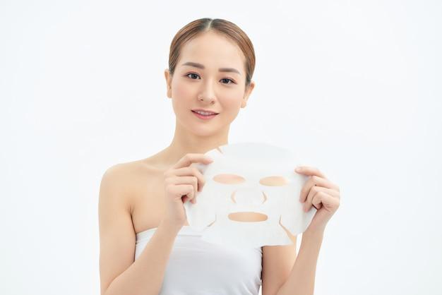 白い背景で隔離のフェイスマスクを保持している若い美しいアジアの女性の肖像画。