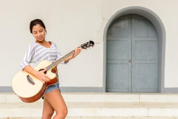 屋外の街の通りでギターを弾く若い美しいアジアの女性の肖像画