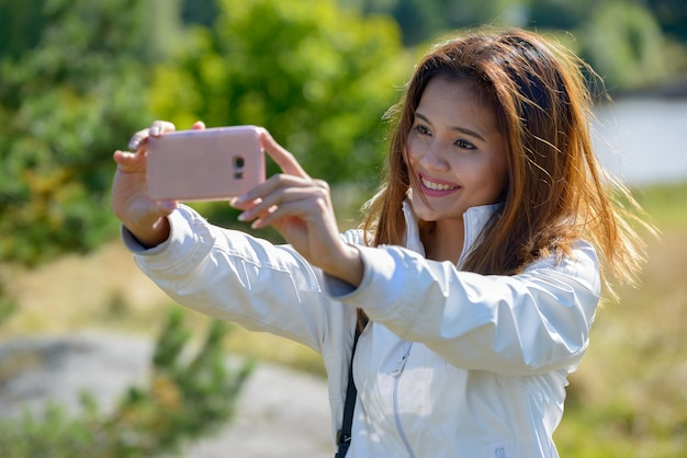 자연 야외에서 편안한 젊은 아름 다운 아시아 여자의 초상화