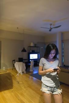 Портрет молодой красивой азиатской женщины, расслабляющейся в гостиной