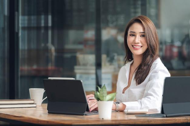 Портрет молодой красивой азиатской женщины, улыбающейся и смотрящей в камеру, сидя за ее офисным столом, успешной бизнес-концепцией,