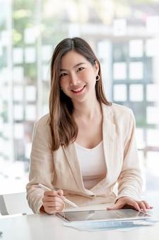 Портрет молодой красивой азиатской женщины, улыбаясь и глядя на камеру во время работы в офисе.