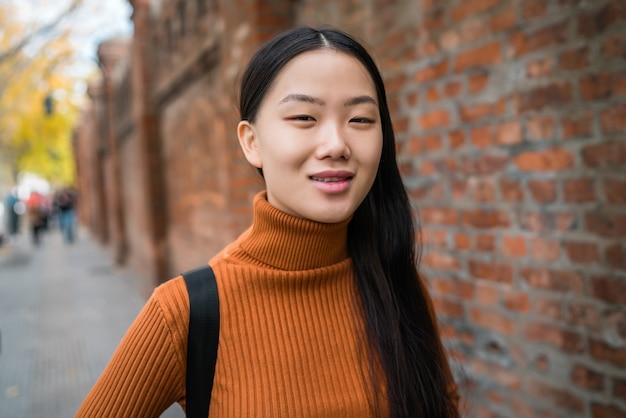 Портрет молодой красивой азиатской женщины, стоящей на улице на улице. городская концепция.