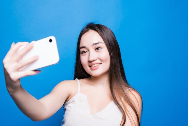 젊은 아름 다운 아시아 여자의 초상화 파란색 격리 된 벽으로 전화에 셀카를 가져 가라.