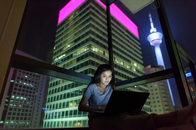 밤에 도시를 볼 수있는 유리 창에 노트북을 사용하는 젊은 아름 다운 아시아 여자의 초상화