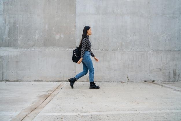 灰色のコンクリートの壁を歩く若い美しいアジアの女性の肖像画。
