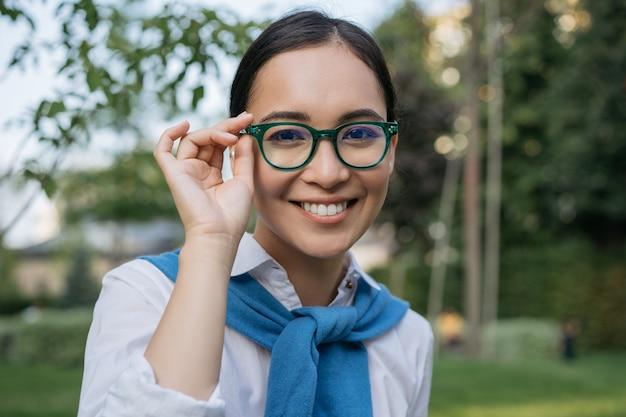 カメラを見て、眼鏡をかけて若い美しいアジアの女性の肖像画