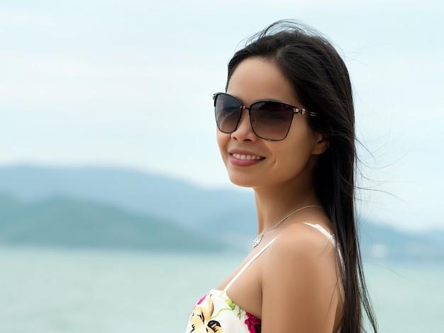 Портрет молодой красивой азиатской женщины нося солнечные очки и стоя на пляже. концепция летнего времени, релаксации или отпуска
