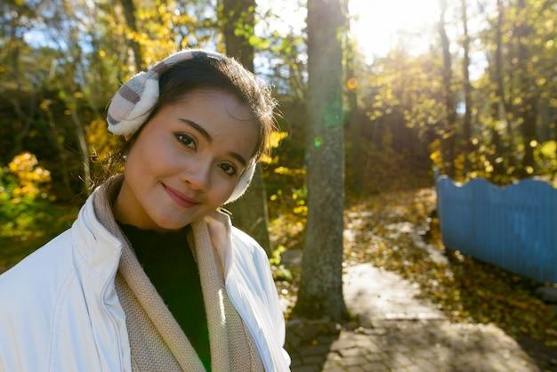 Портрет молодой красивой азиатской женщины с одеждой для холодной погоды, расслабляющейся в лесу