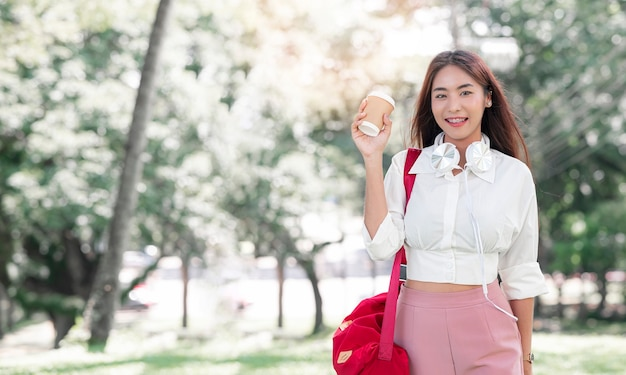 Портрет молодой красивой азиатской женщины с красной сумкой слинга держа кофейную чашку, smilling и смотря камеру пока стоя в парке.