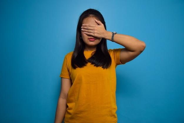 目のジェスチャーをカバーする青い孤立した背景を持つ若い美しいアジアの女性の肖像画