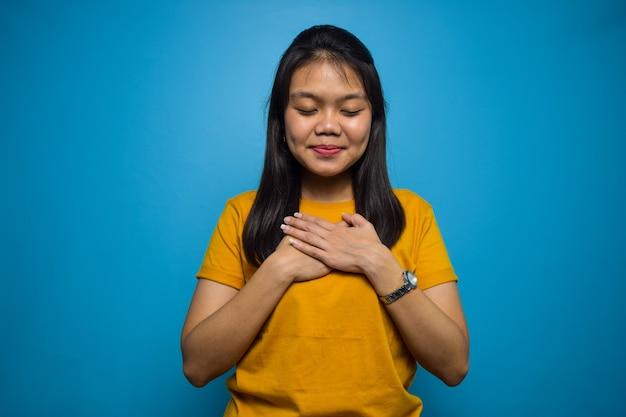 Портрет молодых красивых азиатских женщин с синим изолированным фоном, улыбаясь и быть благодарным