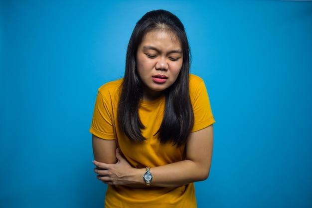 Портрет молодых красивых азиатских женщин с синим изолированным фоном жестом боли в животе