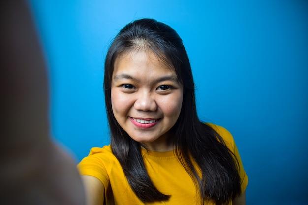 自撮り写真を撮る青い孤立した背景を持つ若い美しいアジアの女性の肖像画