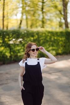 夏の緑豊かな公園で若い美しい魅力的な女性の肖像画