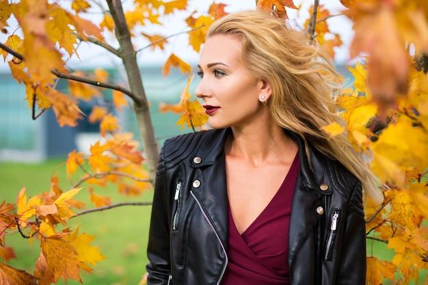 秋の公園でポーズをとって革のジャケットの若い美しいブロンドの女性の肖像画