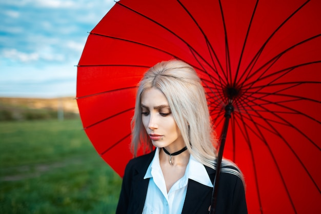 Портрет молодой красивой блондинки, держащей красный зонтик, в черно-белом костюме с колье на шее. открытый фон затуманенное зеленое поле и пасмурное небо.