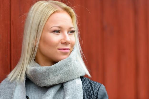 Портрет молодой красивой блондинки скандинавской женщины против красного деревянного здания на открытом воздухе