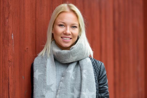 빨간 목조 건물 야외에 대 한 젊은 아름 다운 금발 스칸디나비아 여자의 초상화
