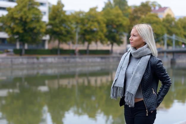 Портрет молодой красивой блондинки скандинавской женщины, расслабляющейся у реки