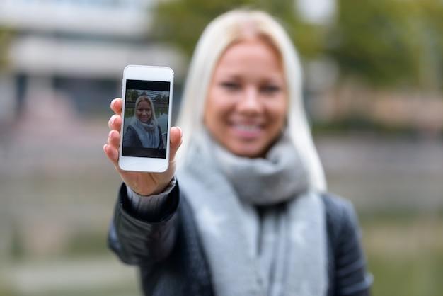 강가에서 편안한 젊은 아름 다운 금발 스칸디나비아 여자의 초상화