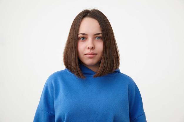 スポーティな服装で白い壁の上に立って、明るい笑顔で前向きに前向きに見ている短いヘアカットの若い美しい青い目のブルネットの女性の肖像画