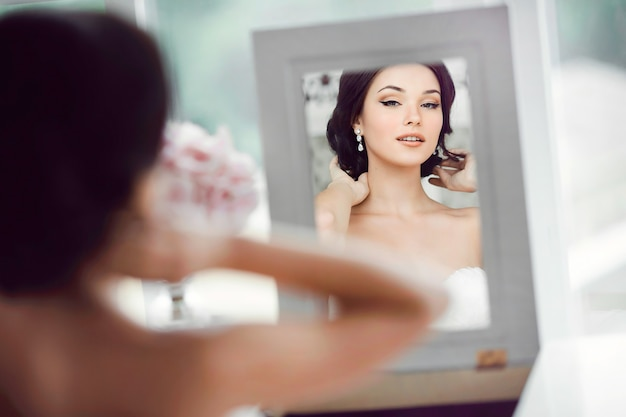 그녀의 결혼식을 준비하는 젊은 아름 다운 신부 초상화. 거울을보고 화려한 여자